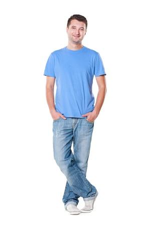 jeune mec: smiley jeune homme en t-shirt et un jean bleu debout, les mains dans la poche