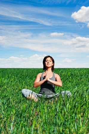 young woman meditating on green meadow photo