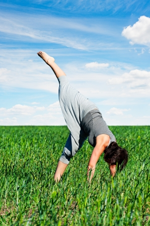 young woman doing exercises in field at sunny day photo