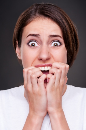 young fear: studio picture of shocked and screaming woman over dark background Stock Photo