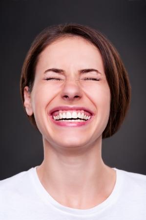 caras de emociones: mujer emocional se reía a carcajadas sobre fondo oscuro