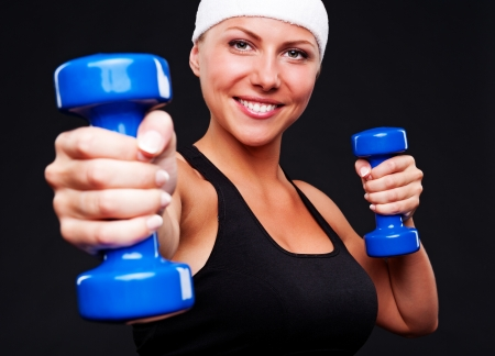 healthy young woman with blue dumbbells. studio shot over black background photo