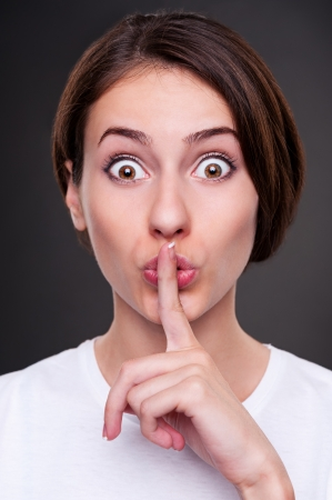 portrait of pretty woman making silence sign over dark background Stock Photo - 14603008