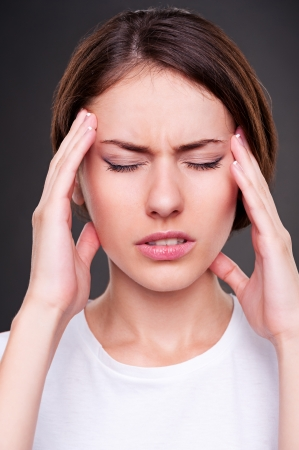 afflict: young woman have a headache. studio shot over dark background Stock Photo