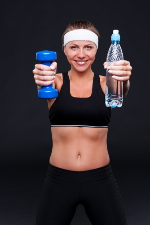 smiley sporty woman holding bottle of water and weight over black background Stock Photo - 14748860