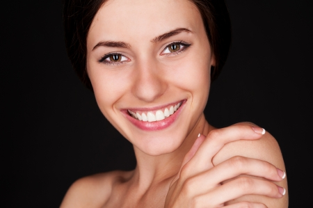 young woman looking at camera and smiling over dark background Stock Photo - 14748859