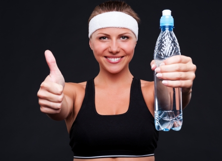 studio shot of fitness woman with bottle of water showing thumbs up Stock Photo - 14748855
