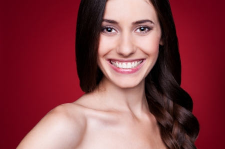 cheerful young woman with long hair over red background Stock Photo - 14748917