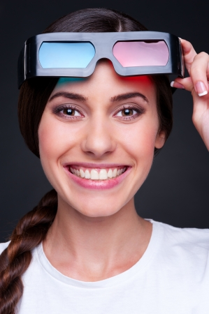 dark glasses: portrait of happy woman with stereo glasses over dark background