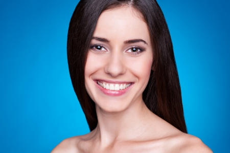 young model looking at camera and smiling. studio portrait over blue background Stock Photo - 14748875