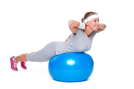 young woman doing exercises on blue ball. studio shot over white background Stock Photo - 14748835
