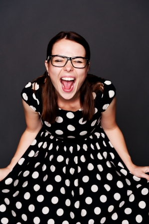 hysterics: studio portrait of emotional young woman in polka-dot dress over dark background