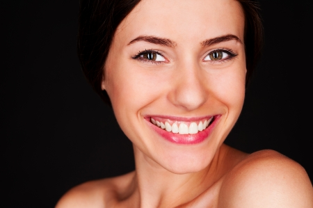 close up portrait of happy young woman over black background Stock Photo