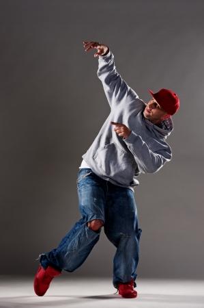 full length picture of hip-hop dancer over dark background Stock Photo