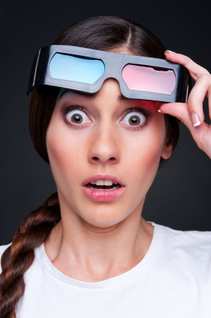 startled: startled woman in 3d glasses over dark background