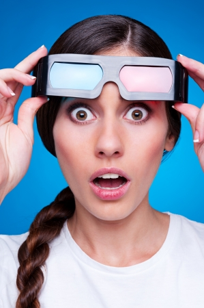 blockbuster: amazed young woman in 3d glasses over blue background