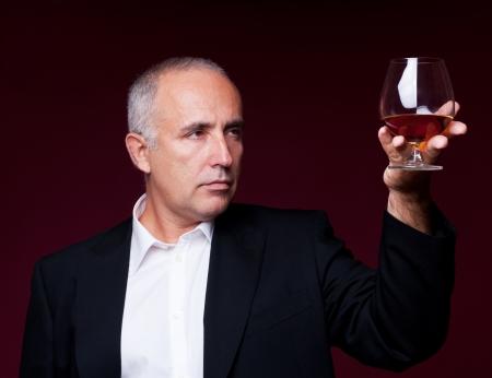 handsome senior man holding old brandy glass over dark background photo