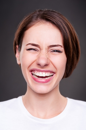 merriment: emotional portrait of happy and laughing woman over dark background