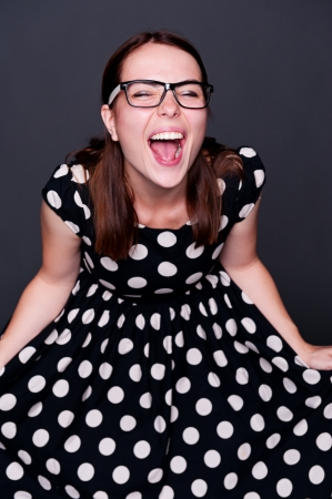 hysterics: studio portrait of happy young woman in polka-dot dress over dark background