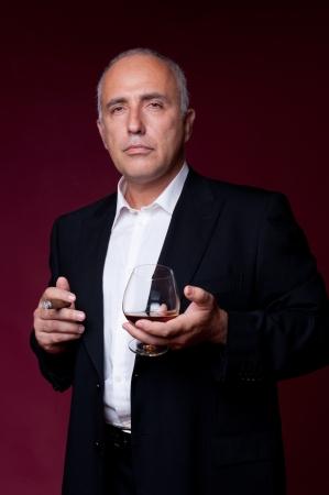 hombre fumando puro: hombre mayor celebración de vidrio y fumando un cigarro en el fondo oscuro