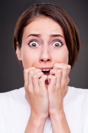fear face: studio picture of shocked and shouting woman over dark background