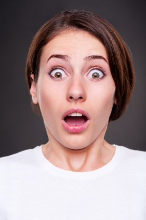 fear face: portrait of surprised woman with open mouth over dark background Stock Photo