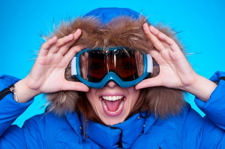 ski mask: happy emotional woman in ski glasses and winter coat over blue background Stock Photo