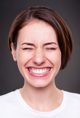 loudly: emotional young woman is laughing loudly over dark background
