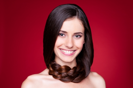 happy beautiful woman with long hair looking at camera. studio shot over red background  photo