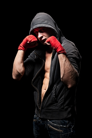studio shot of boxer in hood over black background photo