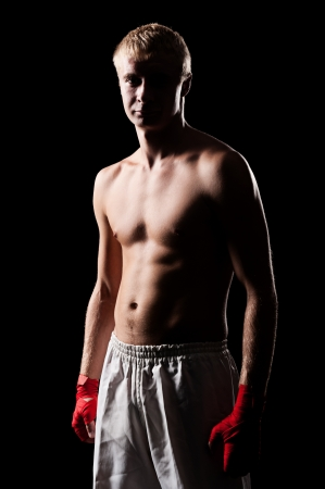 boxer shorts: portrait of caucasian boxer with red bandage on hands. studio shot