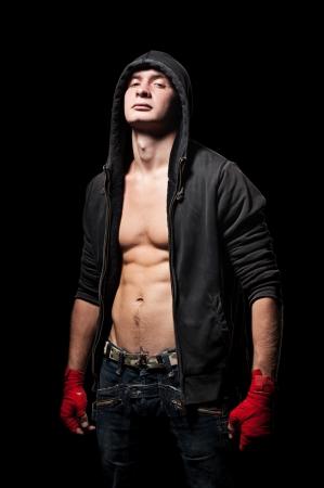studio shot of young man in black hood over dark background photo