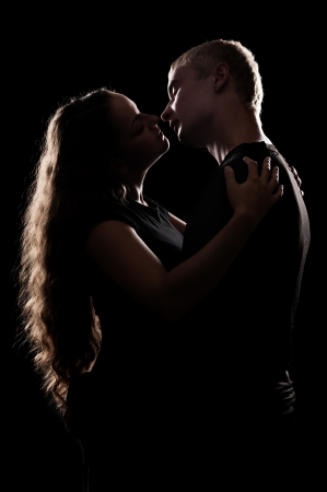 sexual relations: silhouette of romantic couple over black background