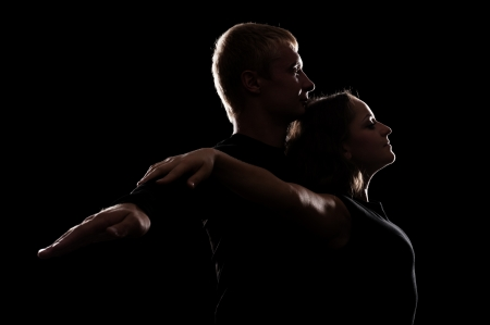 sexual relations: studio shot of young couple in love over dark background