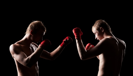 boy boxing: two boxers facing each other in a match over black background Stock Photo