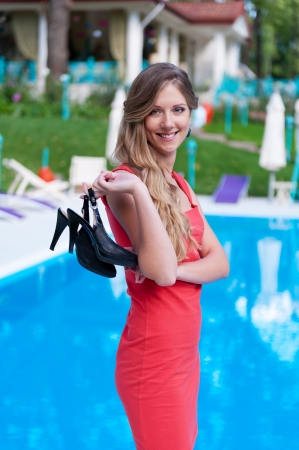 swimming shoes: beautiful slim woman in red dress holding her high-heeled sandals Stock Photo
