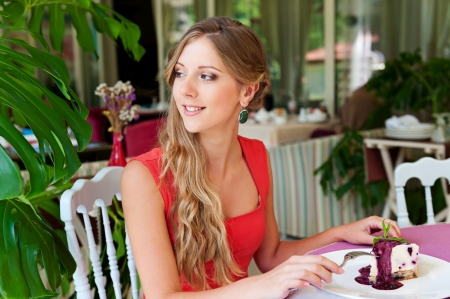 woman eating cake: young alluring woman resting in the cafe and eating cake Stock Photo