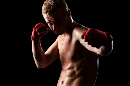 boy boxing: young caucasian fighter boxing over black background