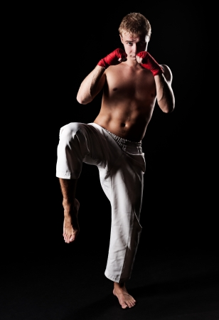 pugilist: young kickboxer ready to fight. black background