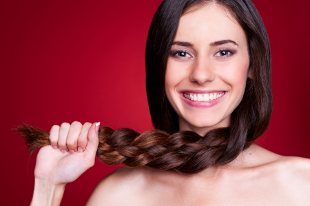 beautiful brunette: happy young woman holding her braid and smiling. studio shot over red background