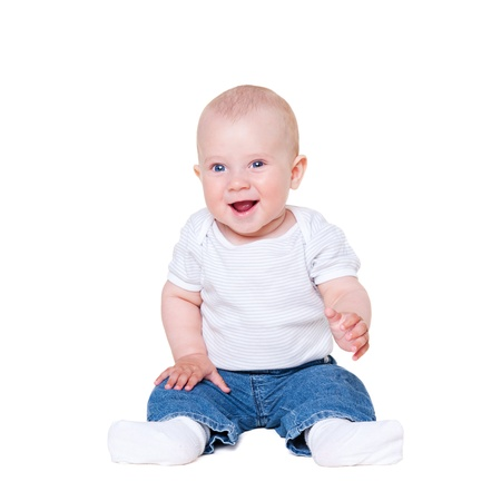 six months: baby boy sitting on white floor and smiling Stock Photo