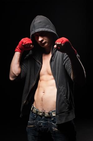 studio shot of boxer in black hood over dark background  photo