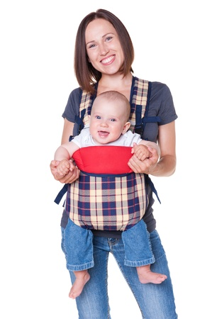 happy mother holding her baby in the knapsack. isolated on white background photo