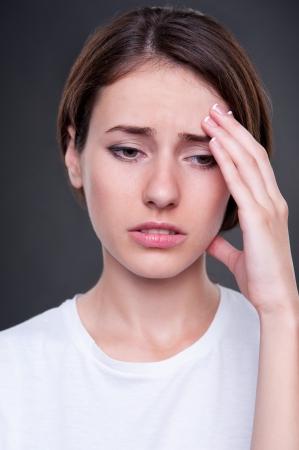 sad woman have a migraine. studio shot over dark background  Фото со стока