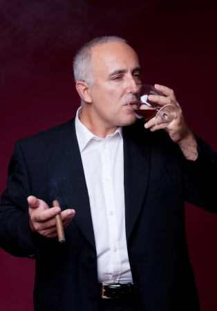 senior man with cigar drinking alcohol from glass over red background photo