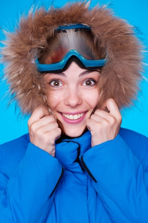 smiley skier feeling cold. studio shot over blue background photo
