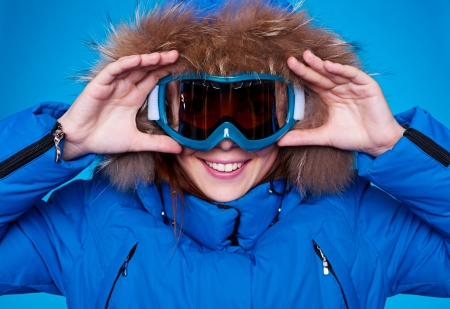 smiley skier looking through mask. studio shot over blue background photo