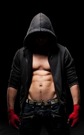 boxeador: hombre fuerte con una venda roja en manos de pie en la oscuridad
