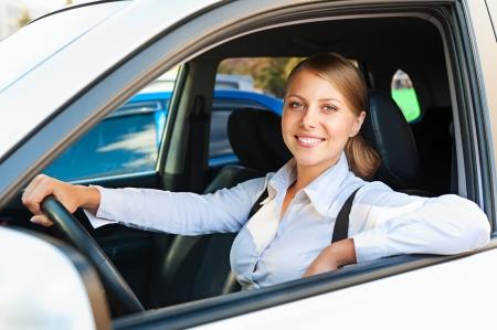 jolie femme assise dans la voiture et souriant Banque d'images