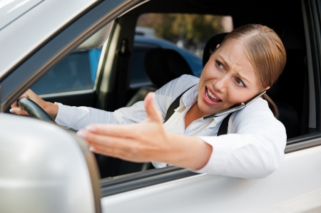 angry female driving the car, holding the mobile phone and screaming at someone photo